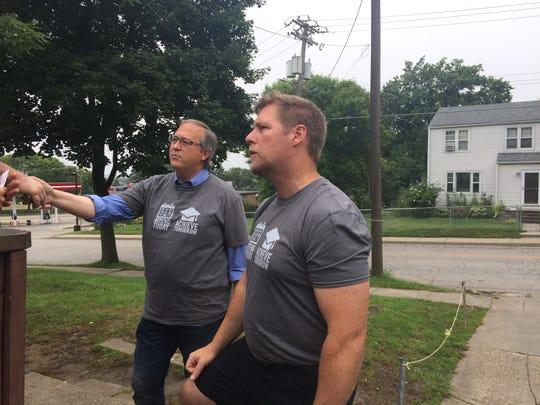 U.S. Congressman David Young, left, and Des Moines Public Schools Superintendent Tom Ahart visit a home during the Des Moines Graduation Walk on  Saturday, Aug. 27, 2016 in Des Moines.