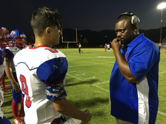 Indio coach Martin White talks with one of his players on the sideline.