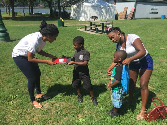 In this 2016 file photo, Satara Brown, founder of Rebuilding Our Children and Community, left, hands a notebook and folder to Christian Brown of the city of Poughkeepsie, while his mother, Leniece Jones, helps her other son, Xavier, with a backpack.