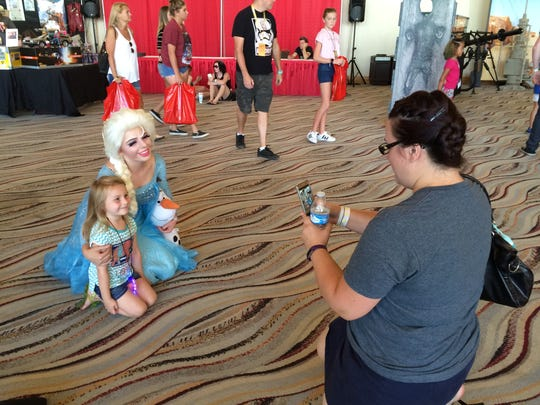 """Redlands resident Kristen Snavely takes a picture of her daughter, Lily, next to Irvine resident Rebecca Gibson. She dressed as Elsa from """"Frozen"""" for Comic Con Palm Springs."""