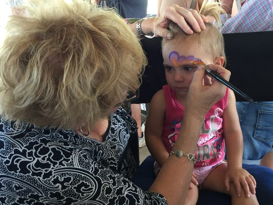 Becky Mezieke paints the face of 2-year-old Melissa Funderburk during Saturday's Holy Angels' event.