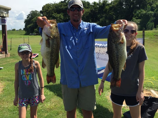 Ringgold's Jamey Myers holds up two of the fish that helped he and Ralph Yelverton finish third in the Holy Angels' Bass Classic with 15.11 pounds. Myers' daughters Anna Kate and Avery look on.