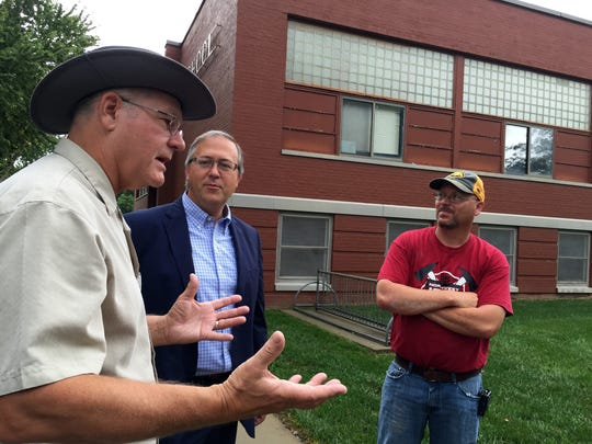 From left, Walnut Mayor Gene Larsen, Rep. David Young and Walnut City Councilman Justen Toolley stand in front of the vacant school and discuss the prospects of reviving it as a community center.
