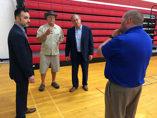 From left, Zach Mannheimer of Iowa Business Growth, Walnut Mayor Gene Jensen, Re. David Young and Avoca-Hancock-Shelby-Tennant-Walnut Schools Superintendent Jesse Ulrich stand in the gymnasium of the vacant Walnut school building and mull its future potential.