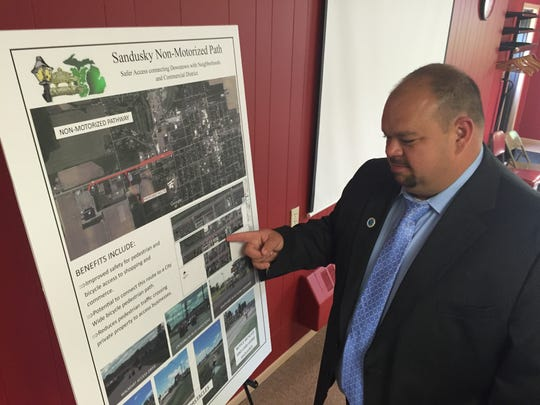 Sandusky City Manager Dave Faber points out the city's proposed plans to construct a sidewalk from the western edge of the city's neighborhoods down Sandusky Road to Walmart in the city's commercial district. Rising Tide helped secure some of the funding for the project.