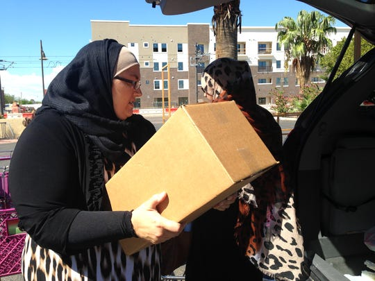 Members of the Islamic Center of the East Valley load boxes of groceries into a van to donate to the refugee family.