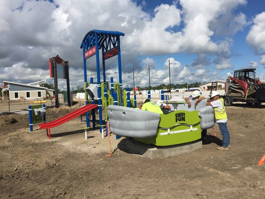 Crews install Americans With Disabilities Act-compliant playground equipment next to new ADA-accessible baseball field.
