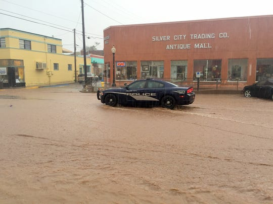 Silver City Police driving down Broadway Street in the rain.