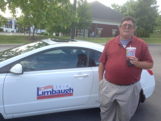 David Limbaugh poses by car with his presidential campaign sign on the door.