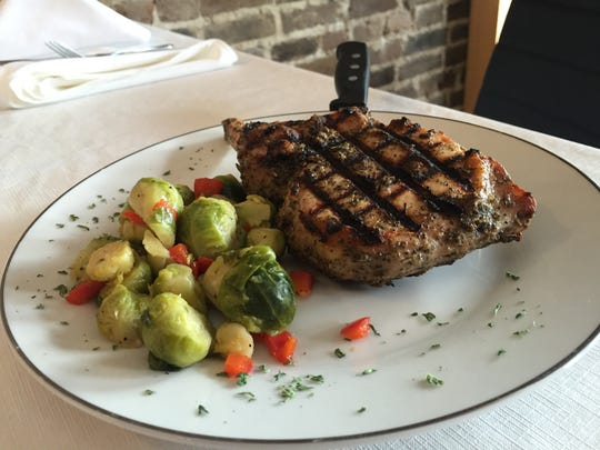 Roasted Brussels sprouts and pork chop at The Gavel Grill and Speakeasy.
