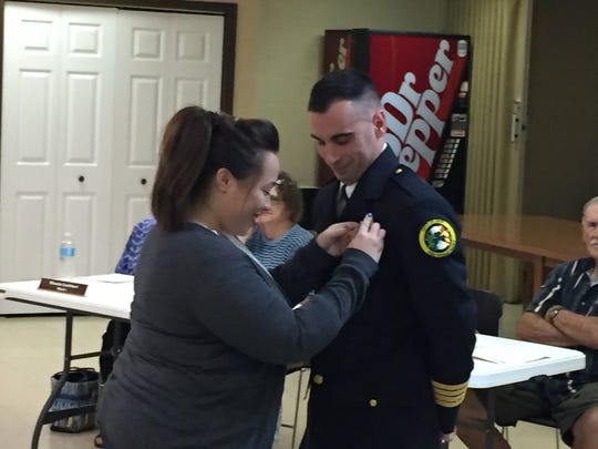 Mariana Hagler, left, pins a Deptuy Chief badge on Dustin Sinclair of the Erin Fire Department.