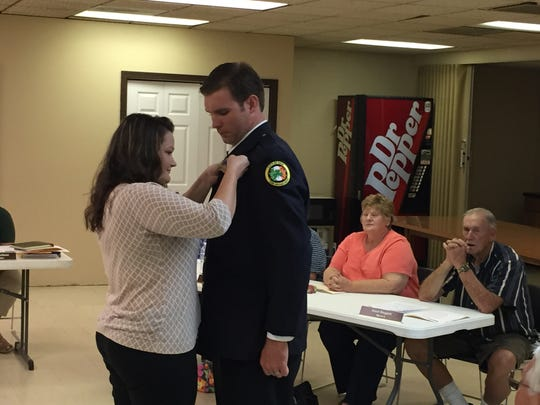 Erin firefighter Andrew DeMersman has a lieutenant badge pinned on by his wife Nicole.