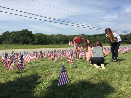 A group of Woodglen Middle School students place flags on the school's front lawn in remembrance of those who died on 9/11.