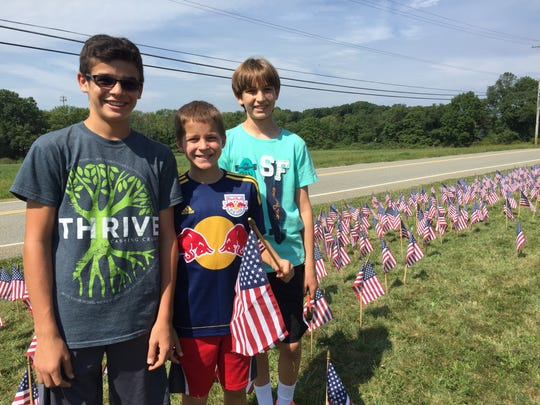 Three Woodglen Middle School students place flags on the school's lawn in remembrance of 9/11.