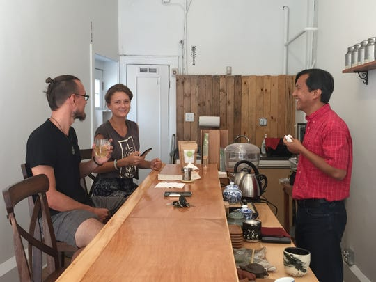 Customers Dustin Burns, 32, and Christina Vysochan, 23, of Rochester, talk with Niraj Lama, owner of Leaf Tea Bar.