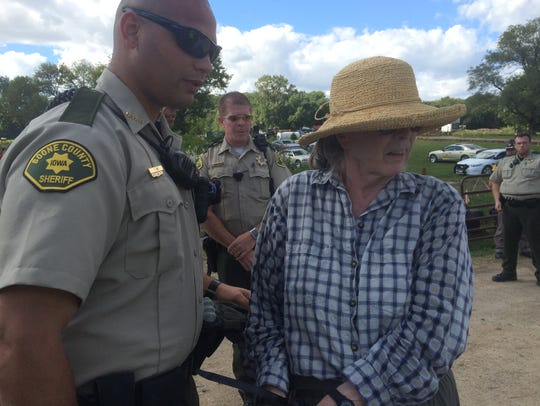 Protester Anne Clark is arrested on Saturday, Sept.