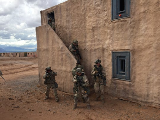 Soldiers from 1-36 Infantry leave a building after