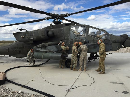 An Apache attack helicopter gets refueled and rearmed