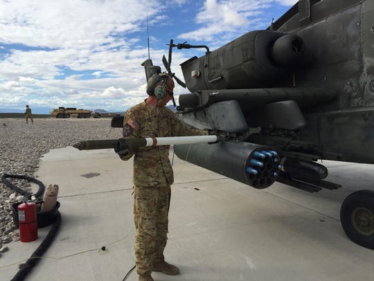 An Apache attack helicopter gets rearmed during aerial