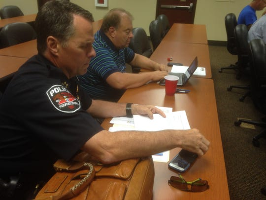 Murfreesboro Police Chief Karl Durr, left, and Assistant City Manager Jim Crumley examine materials before the start of a City Council retreat Monday at the Stones River Water Treatment Plant.