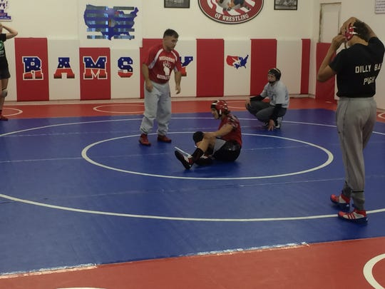 Joe Ramsey explains technique to wrestlers as Macey Kilty (back right) looks on.