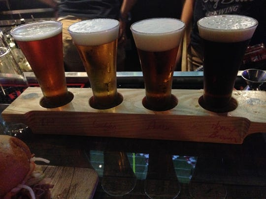 A bartender serves tastings of Big Blue Brewing's first four craft beers: amber ale, golden ale, IPA and honey brown ale.