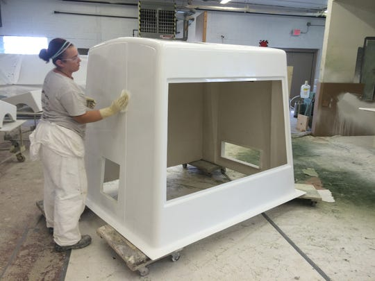 A Mekco employee finishes up work on a fiberglass-reinforced plastic enclosure that will be used to protect an ammonium hydroxide pump skid.