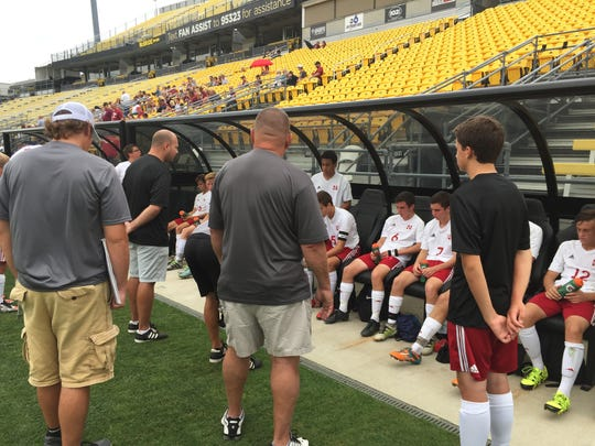 Newark coach Alex Kovach (center) talks to his team at halftime at MAPFRE Stadium, with the Wildcats trailing Mount Vernon 1-0.
