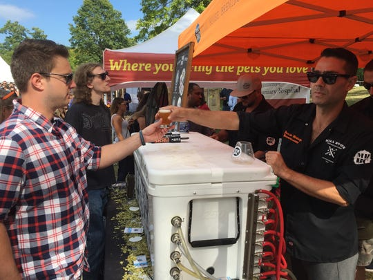 Matt Laspada, 24, of Wallkill, orders a beer from Jamie Bishop, brewer at Mill House Brewing Company in Poughkeepsie, at the Hudson River Craft Beer Festival in Beacon Saturday.