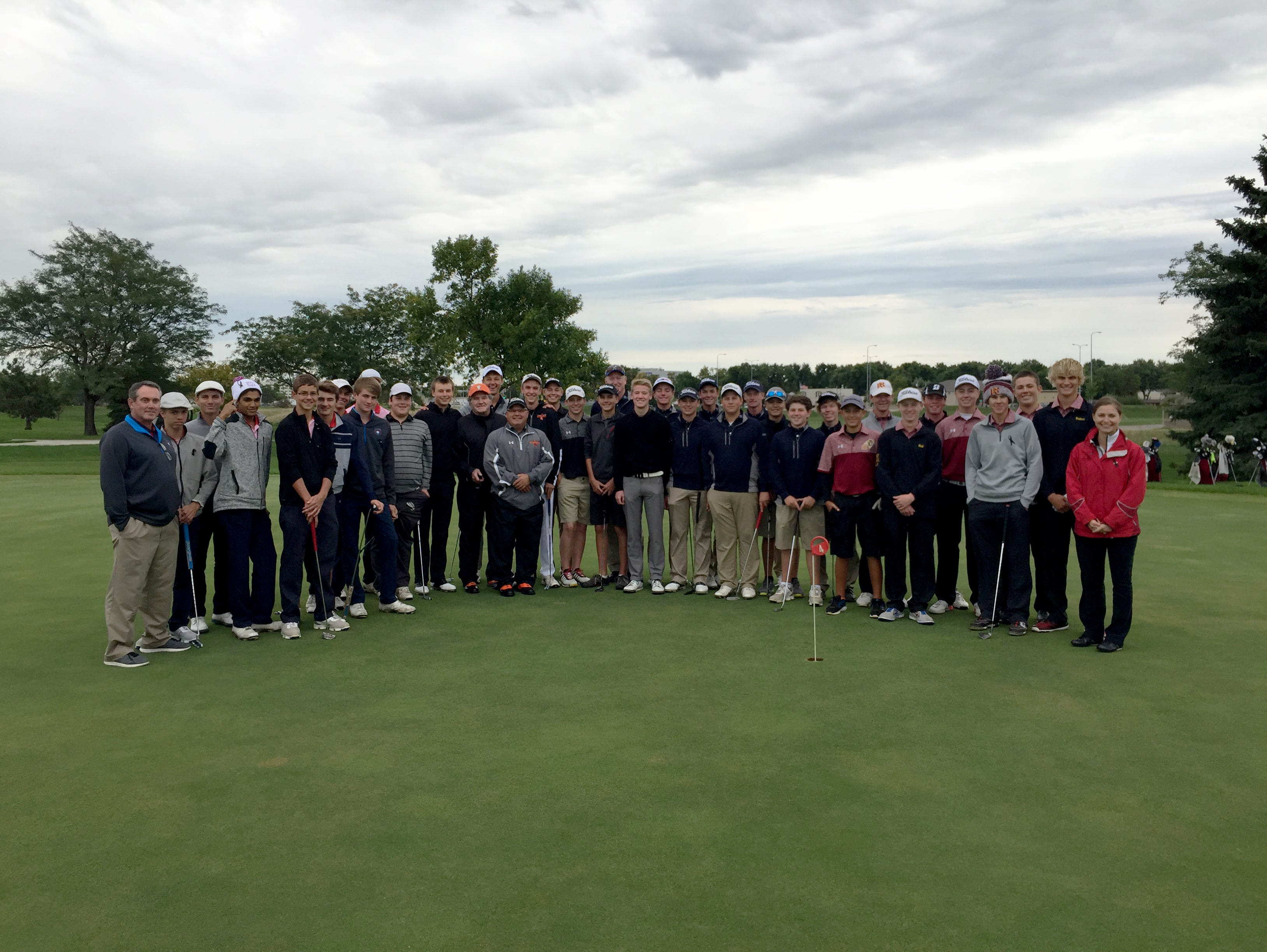 Golfers from O'Gorman, Washington, Lincoln and Roosevelt pose for a picture with former Washington assistant golf coach Ken Martens prior to the start of the second round of the Boys City Golf Meet at Elmwood Golf Course on Tuesday, Sept. 13.