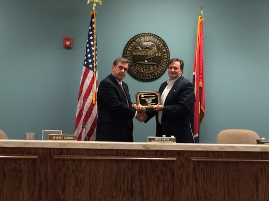 Robertson County Director of Schools Mike Davis honors outgoing board member Lyle Payne during the August school board meeting.