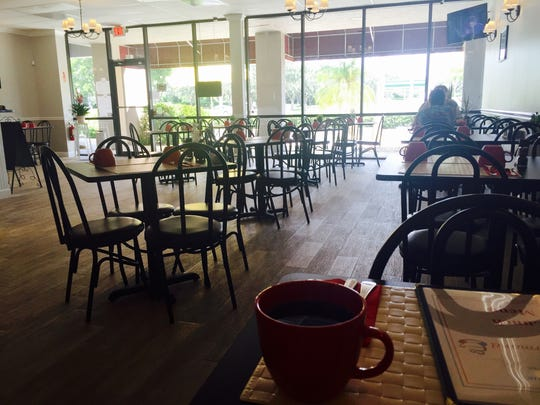 The interior of Cafe Gourmand is done in creams and beiges, with touches of red in its giant mugs, and dark bistro tables. Harriet Howard Heithaus/Staff