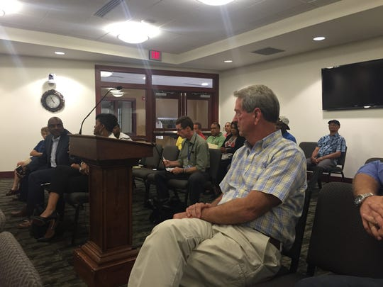York-area developer David Yohn, right, listens as realtor Tony Thomas, far left, talks about his wife's numerous attempts to formally seek the Citizens Bank building.