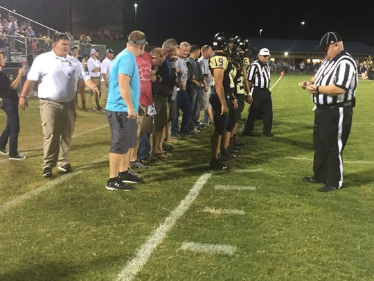 Former Rebel football players  accompany their coach, Floyd Powers, center in light gray shirt, to mid-field for the coin toss.