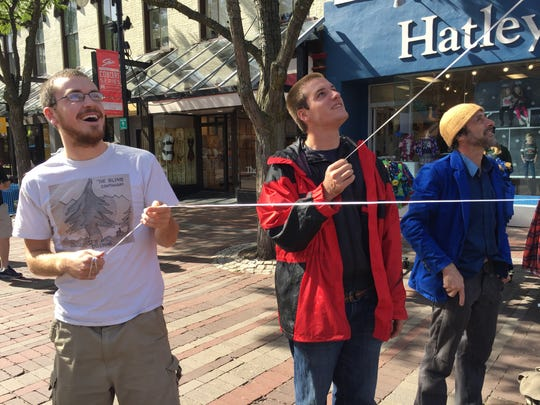 Jack Hanson (left) and Adrian Burnette (right) hold strings for green and red balloons respectively on Church Street for a demonstration by the Coalition for a Livable City on Monday, Sept 26.