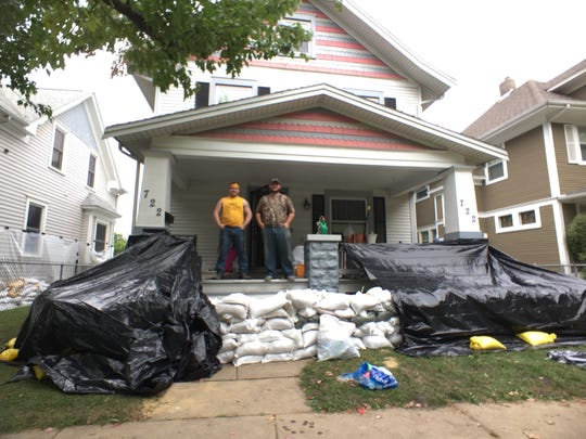 Friends Zach Miller, left, and Austin Pinney stand on the front porch of Pinney's sandbagged house on Sunday, Sept. 25, 2016, just west of the river in Cedar Rapids.