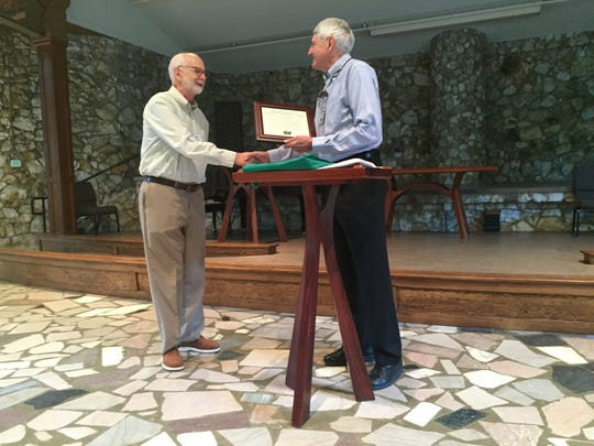 Bill Seaman, right, presents John Johnson with a plaque commemorating his work on behalf of Montreat's hemlocks and greenery.