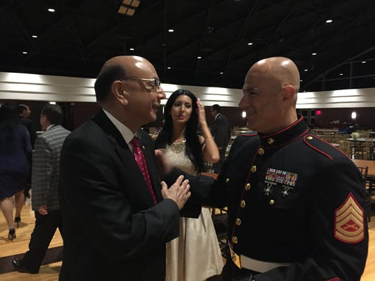 Khizr Khan speaks with a U.S. Marine at a banquet of the Arab-American Civil Rights League in Dearborn, which Khan addressed on Sept. 29, 2016