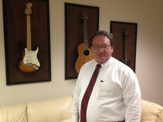 Mark Donahoe, of The Donahoe Firm, stands in front of a portion of his collection of guitars.