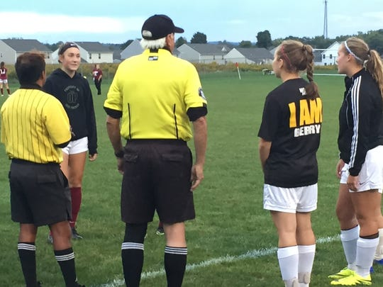 Captains meet with the officials prior to Saturday's Newark-Watkins Memorial game, including Abby Davies of the Wildcats (left), along with Dana Berry and Bop Weller of the Warriors (right).