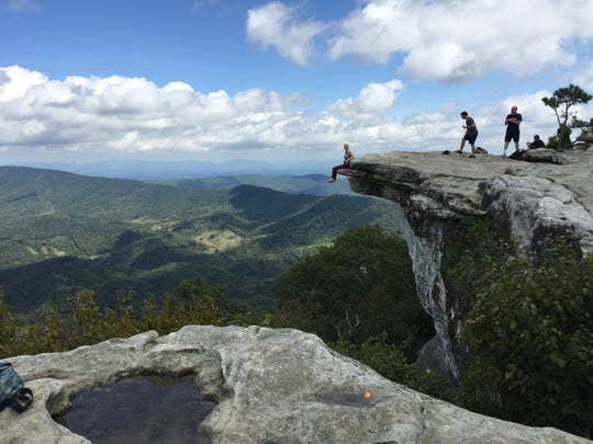 A young hiker from Richmond, Virginia, dangles her feet over the edge of McAfee Knob - one of the most photographed places along the 2,190-mile Appalachian Trail.