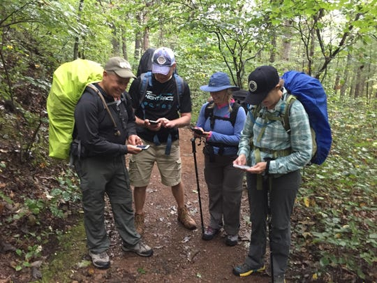 Fellow hikers check their Appalachian Trail apps before tackling the three-day Triple Crown section near Roanoke. Virginia.