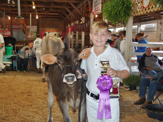 Grant Lahmers poses with one of his Brown Swiss heifers