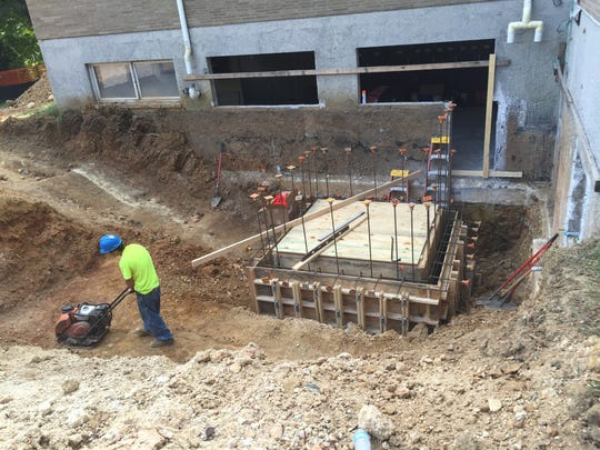 A worker compacts the soil around the base of an elevator shaft being added to the rear of the Visitor Center.
