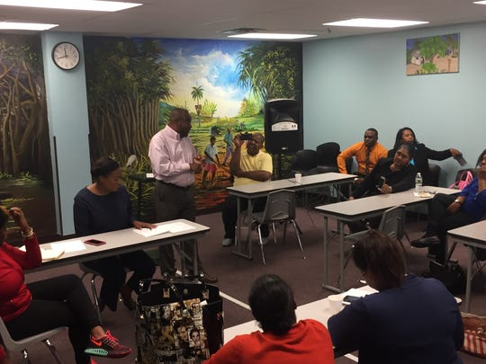 Renold Julien, center, speaks to nonprofit and community group officials at Konbit Neg Lakay in Spring Valley on Friday about relief efforts for Haiti after Hurricane Matthew.