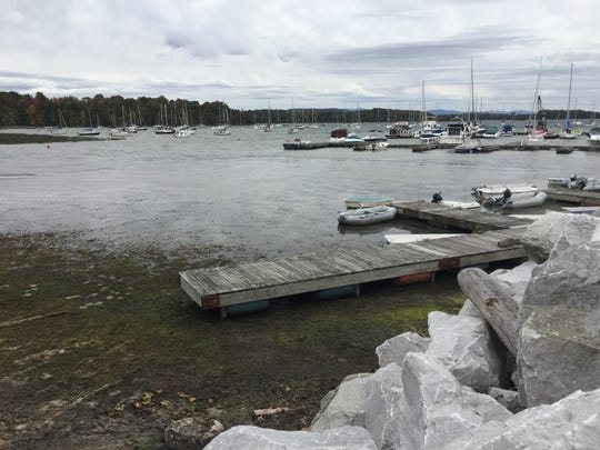 Dinghies float in shallow water along a dock at Point
