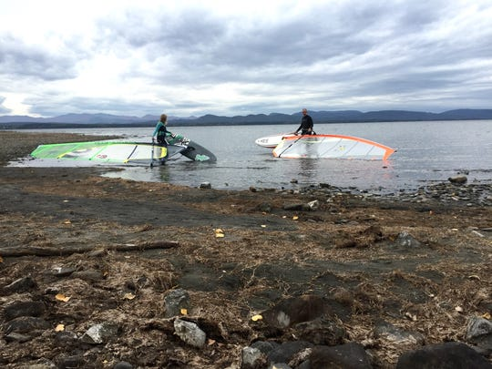 Shanley Hinge, left, and Gary Franklin walk into Lake Champlain for an afternoon of wind surfing Saturday, Oct. 8.