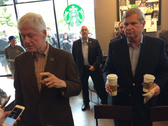 U.S. Secretary of Agriculture and former Iowa Gov. Tom Vilsack holds a cup of coffee for former President Bill Clinton during  a campaign stop in Ames on Wednesday.