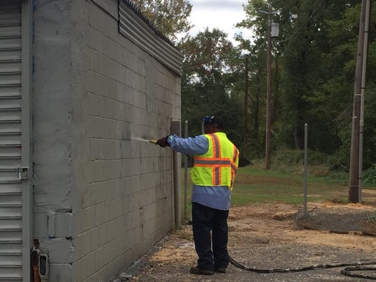 A Camden Public Works employee uses a pressure washer to remove racist graffiti from the field house.