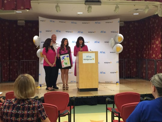 McKenzie Monk's family accepting their Duckprint Award